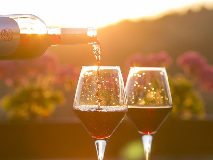 wine glasses being filled with red wine outdoors at sunset