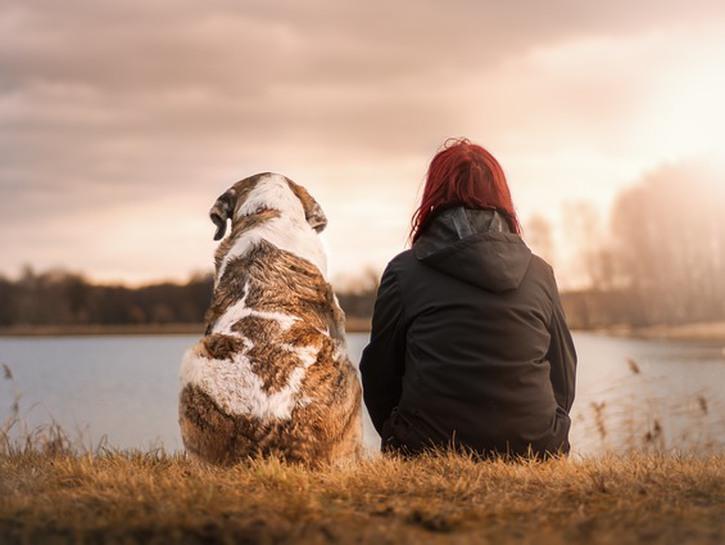 Woman and dog sit by lake