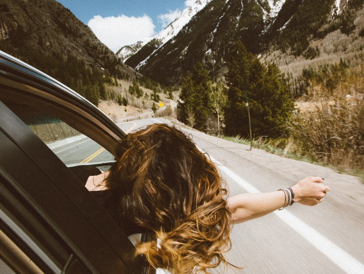 Woman hanging out of car window