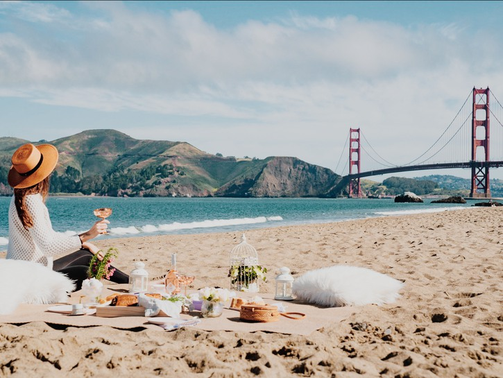 Woman having a picnic on the beach across from the Golden Gate Bridge.