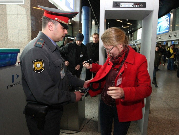 Woman having her coat searched by security at airport checkpoint