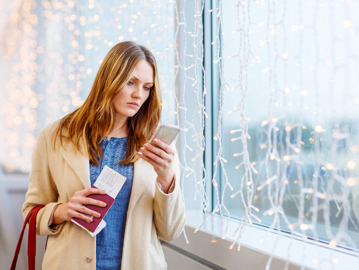 Woman holding passport looks at phone