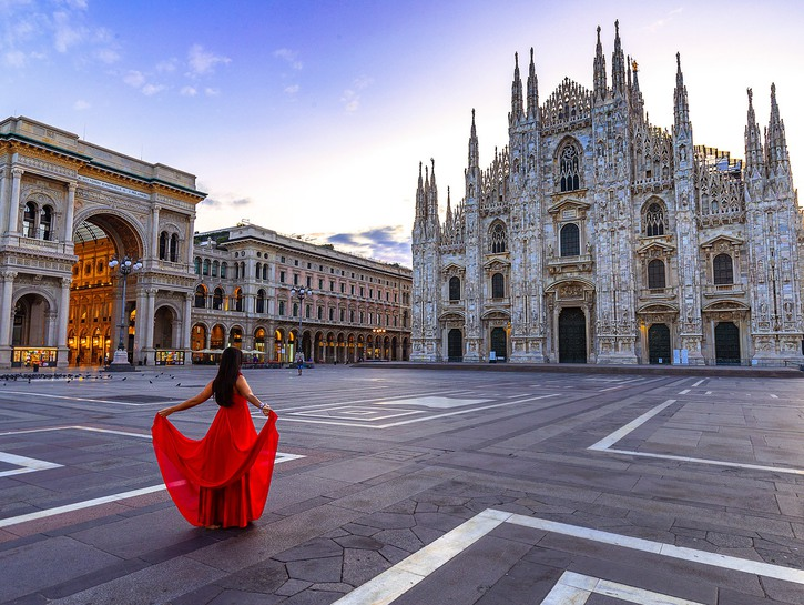 woman in a red dress stands in front of the duomo of Milan