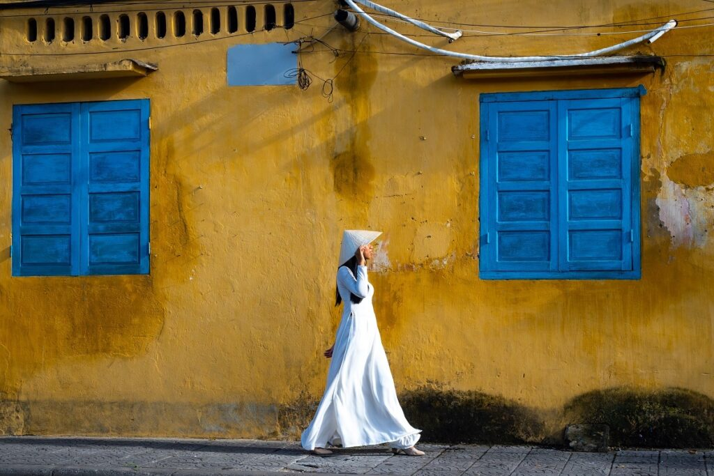 Woman in a white tunic and hat walking.