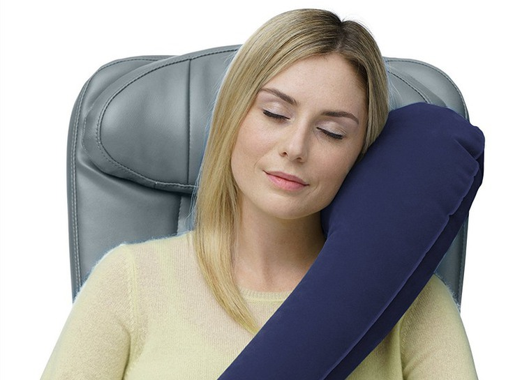 Woman in plane seat wearing Travelrest ultimate neck pillow.