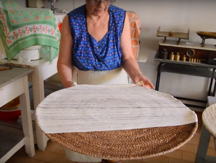 Woman laying su filindeu noodles out on a circular table to dry
