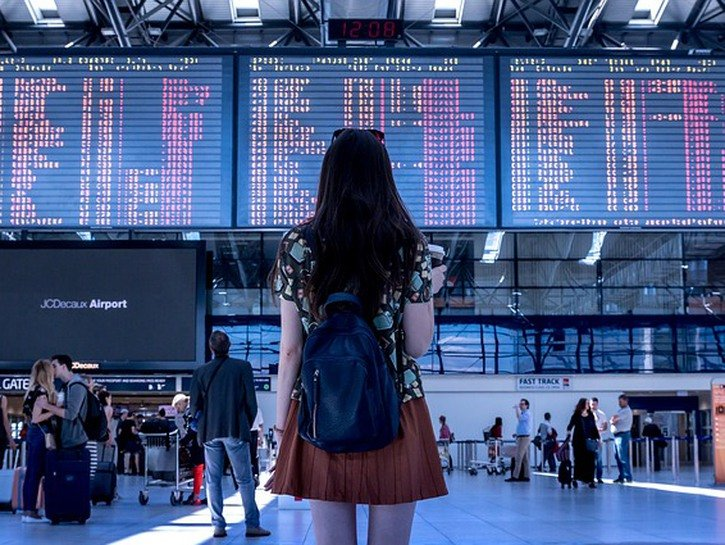Woman looks at flight schedule at airport