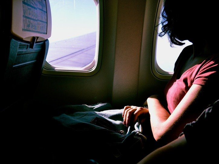 woman looks out window on plane