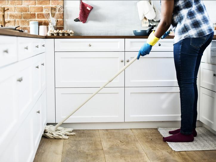 Woman mopping hardwood floor in kitchen