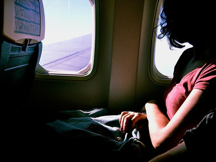 Woman on an airplane looks out the window