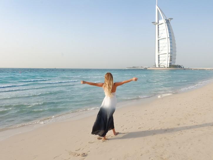 Woman on beach in Dubai with Burj Al Arab Jumeirah hotel in background