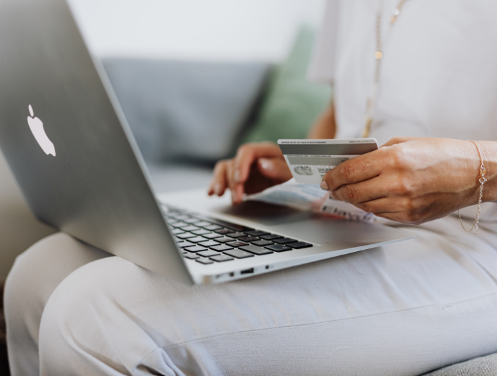 woman on laptop holding credit card / online shopping