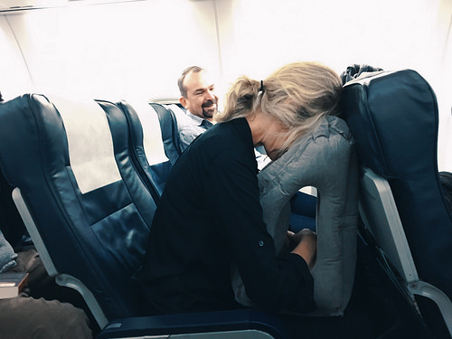 woman on plane burying her face in pillow