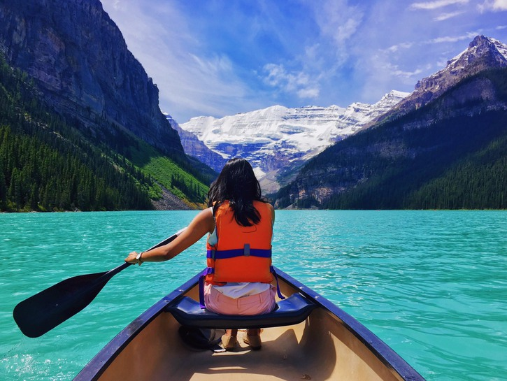 Woman paddles in rowboat on Lake Louise in Banff