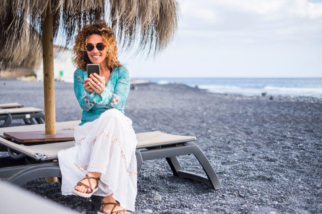 woman sitting on beach chair checking her cell phone and smiling