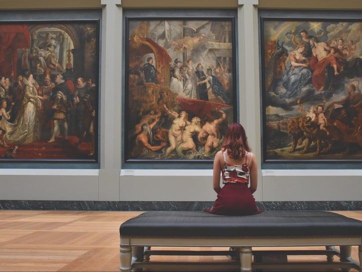 Woman sitting on bench, viewing paintings in the Prado Museum, Madrid, Spain