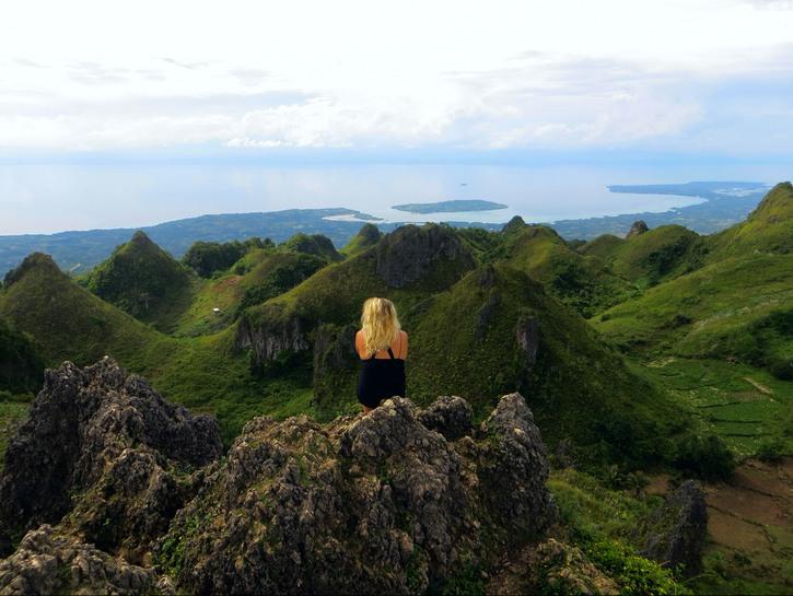 Woman sitting on Osmeña Peak in Cebu.