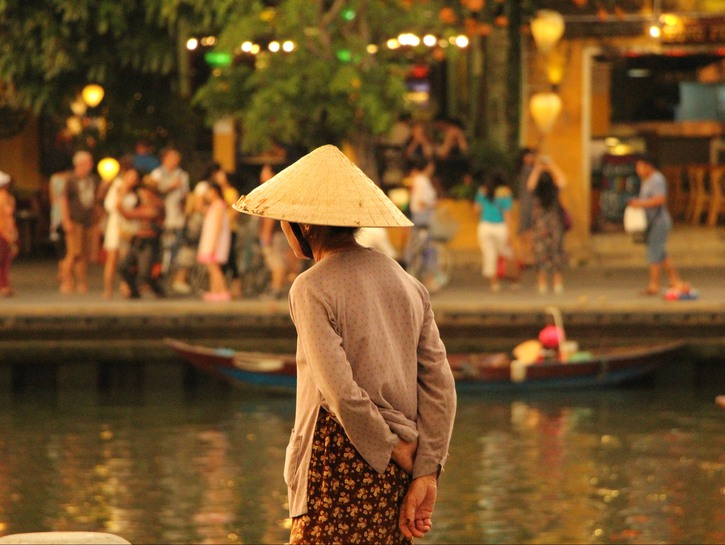 Woman standing by canal in Hoi An, Vietnam