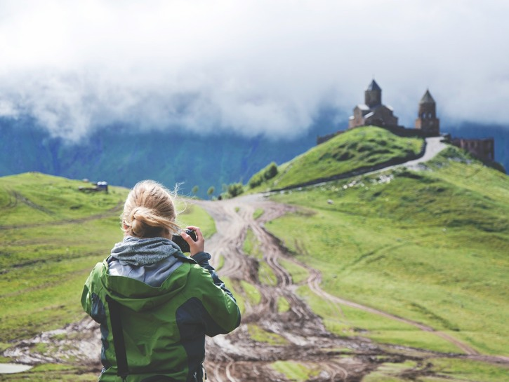 Woman takes picture of old church on hill