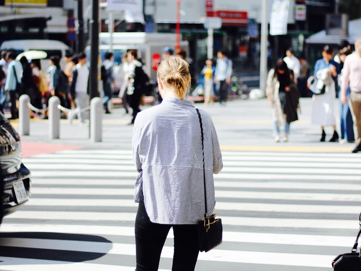 Woman texting on the sidewalk at busy intersection
