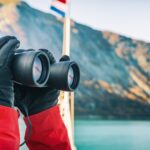 woman using binoculars in front of mountains