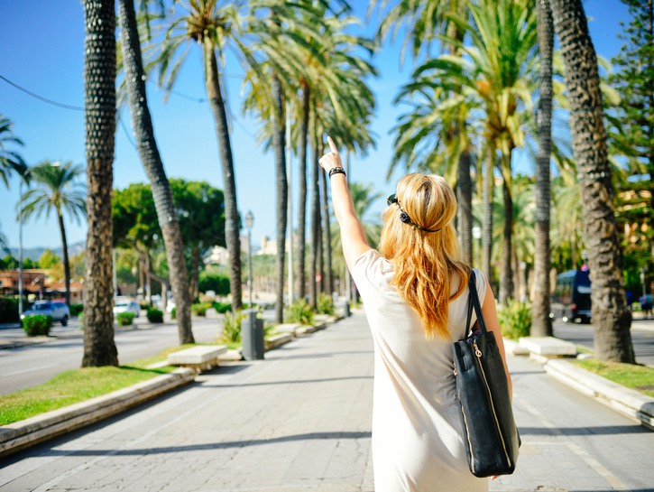 Woman walking down street pointing at palm tree