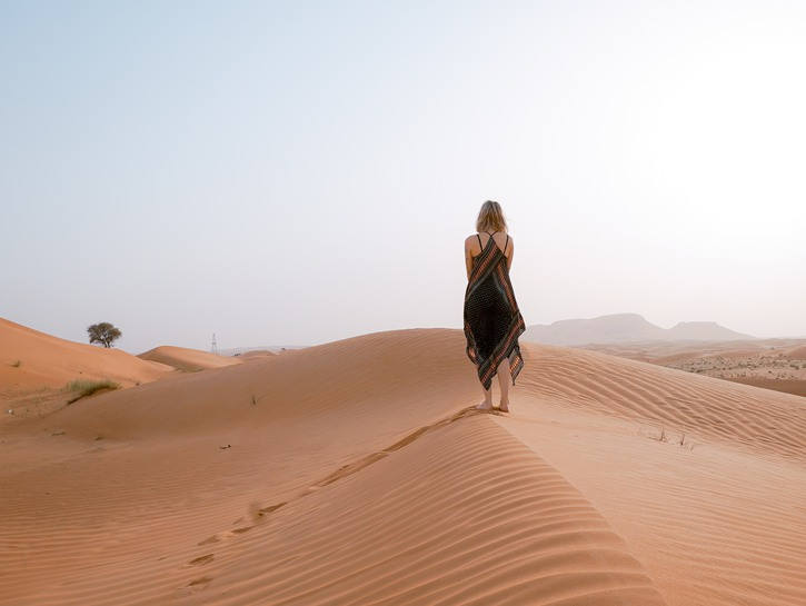 Woman walking in desert, Dubai.