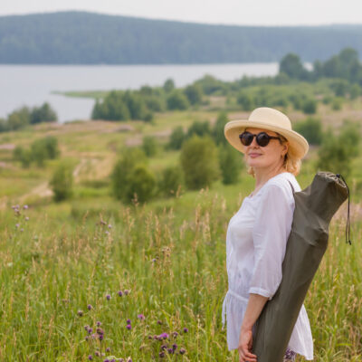 woman walking through prairie overlooking a lake