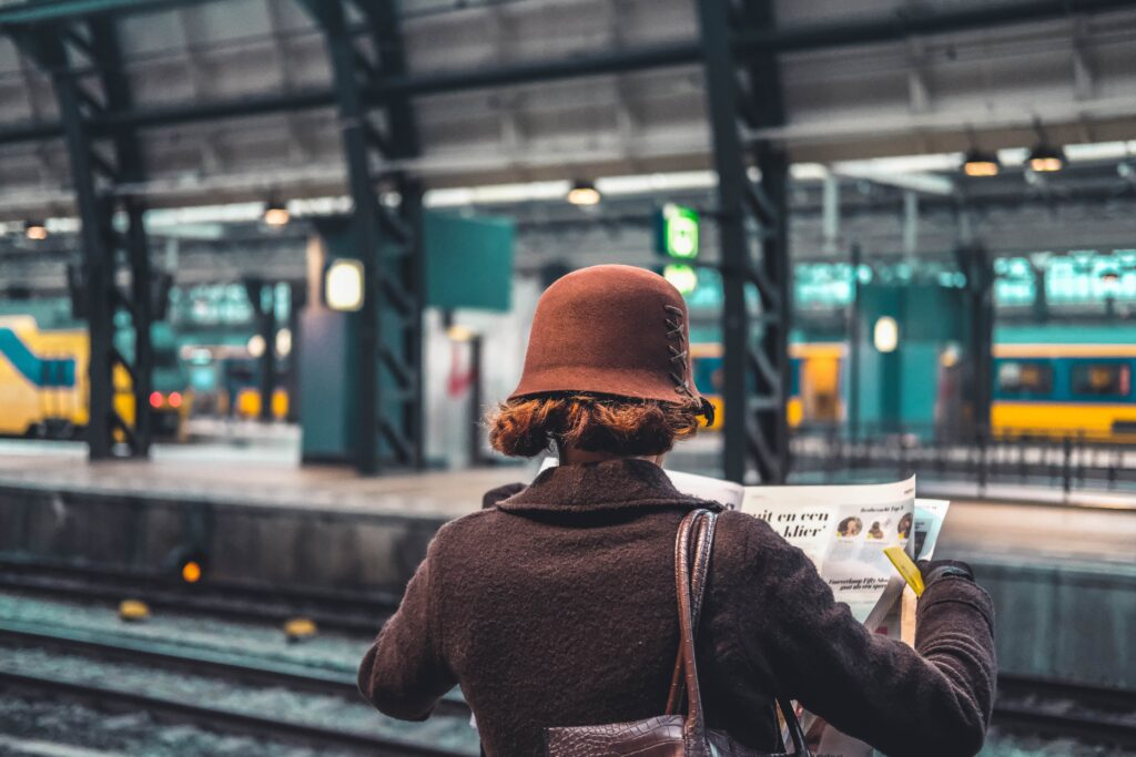 woman wearing a stylish brown coat and bucket hat reading a newspaper while waiting on a train platf