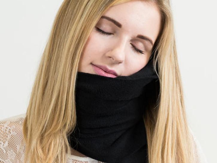 Woman wearing Trtl pillow