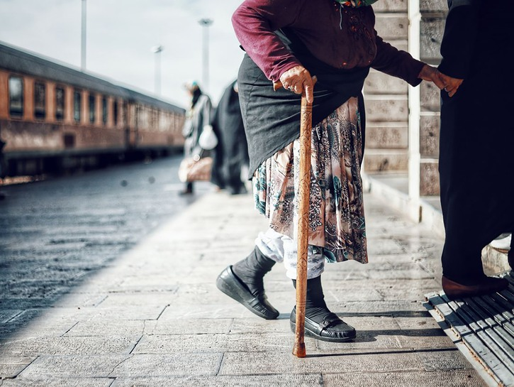 Woman with cane being led of train platform