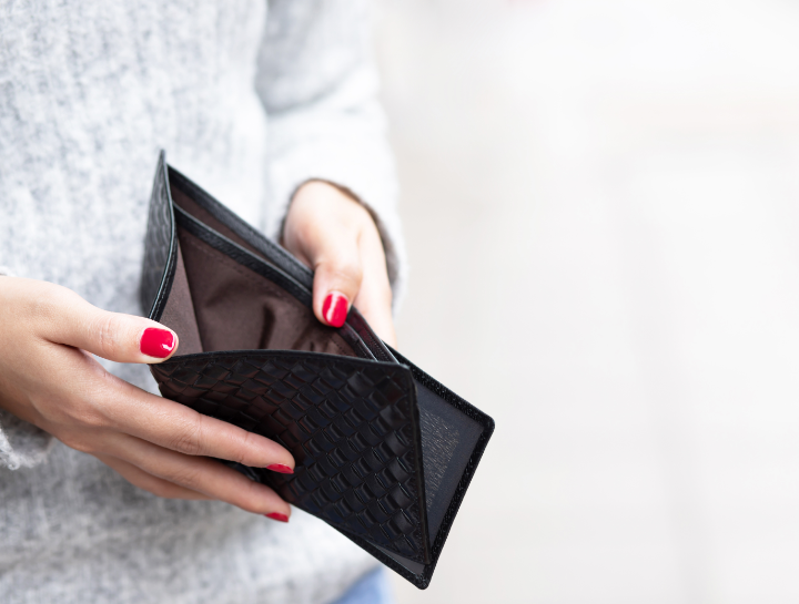 woman with red nails opening empty wallet