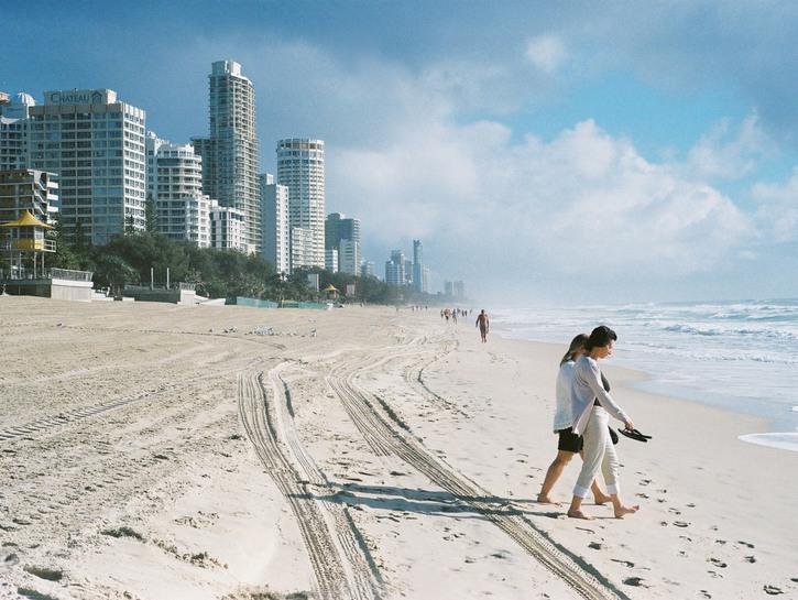 Women walking toward the ocean on a Miami beach, condos in the background