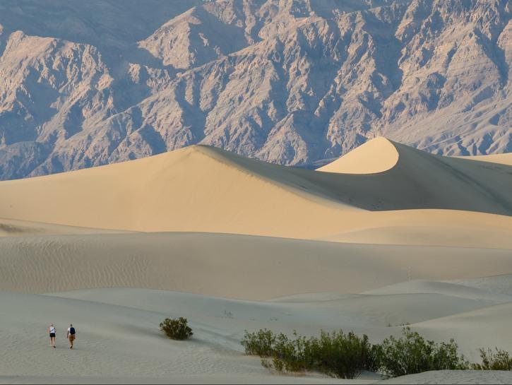 Women walking up sand dune against mountainous backdrop, Death Valley National Park.