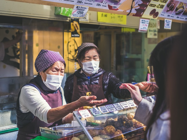 Women wearing face masks selling food at stall