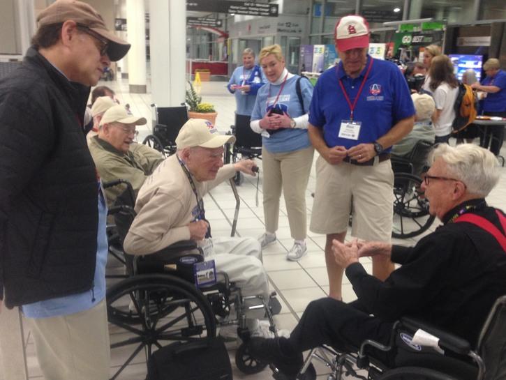 WWII veterans in wheelchairs talking.