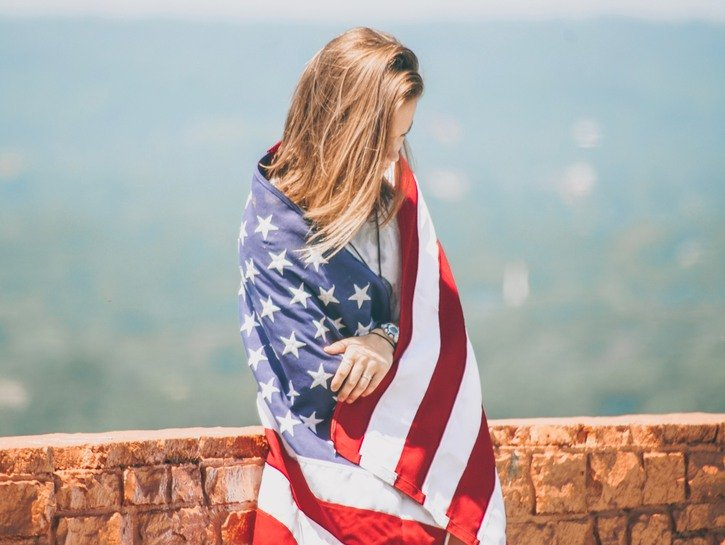 Young woman leans against wall, draped in American flag