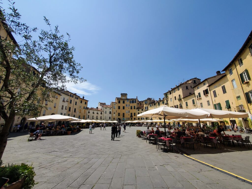 Piazza dell'Anfiteatro Best International Small Town Finalist: Lucca, Italy Lucca, Italy People sitting at tables with umbrellas surrounded by yellow colored buildings