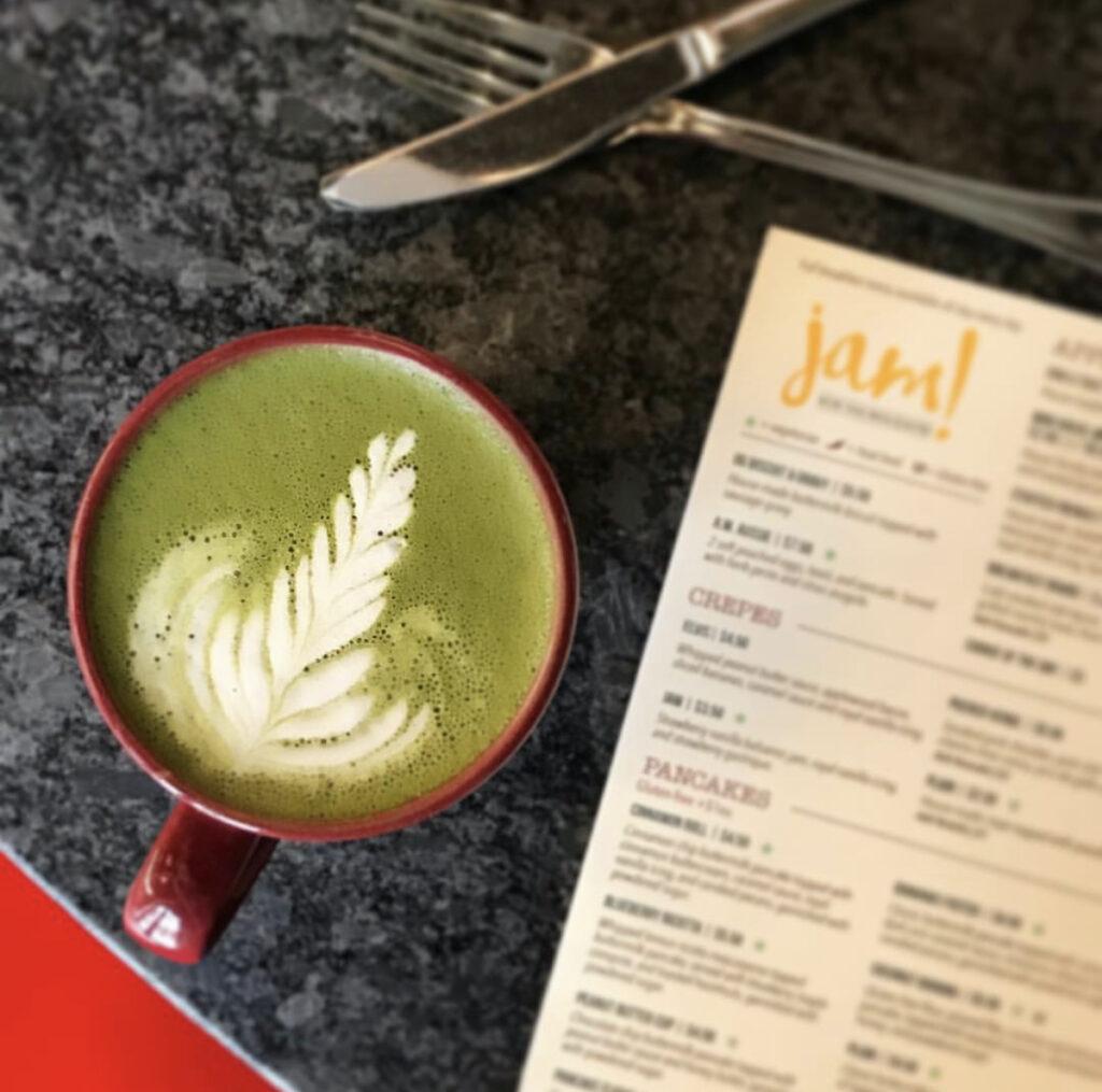 Coffee sitting next to menu, Jam!