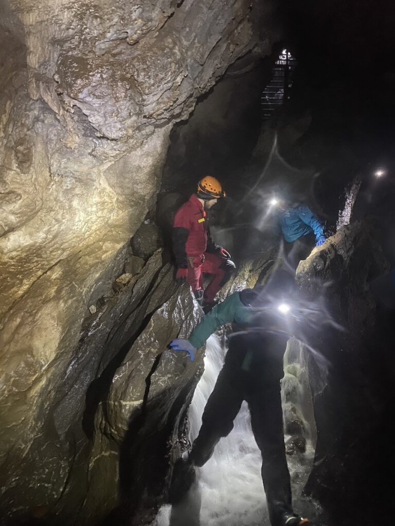 Three people wild caving.