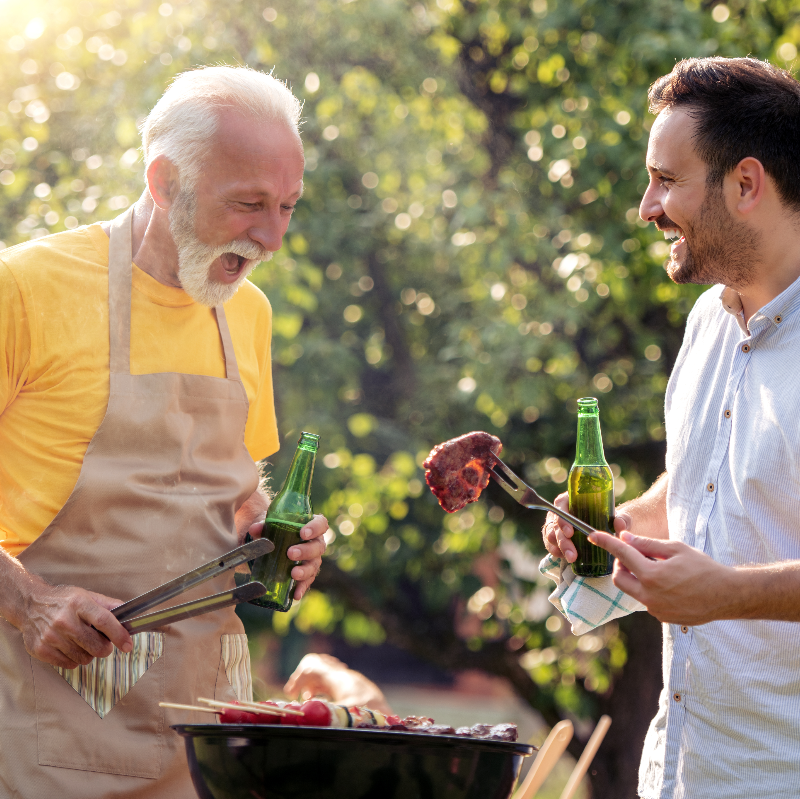 Dad and son make barbecue and drink beer in garden.
