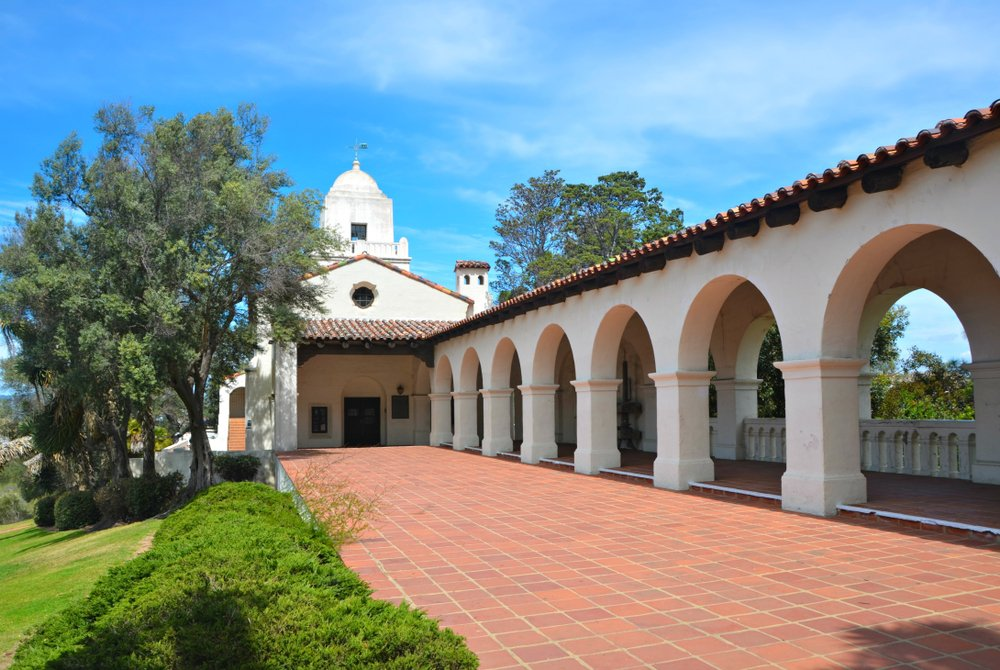 Exterior view of the Junipero Serra Museum in the Presidio Park of San Diego with the arched entrance walk way, the Terracotta tiled floor and the Spanish Colonial historic fort in the background.