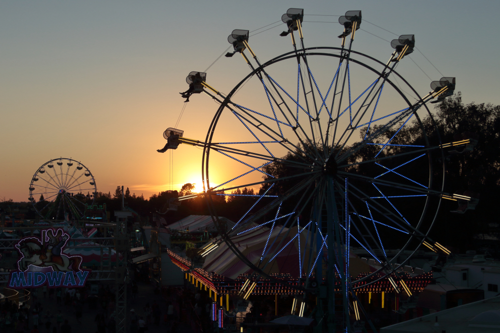 Two ferris wheels silhouetted against sunset sky. California State Fair in the summer. Overlooking the midway.