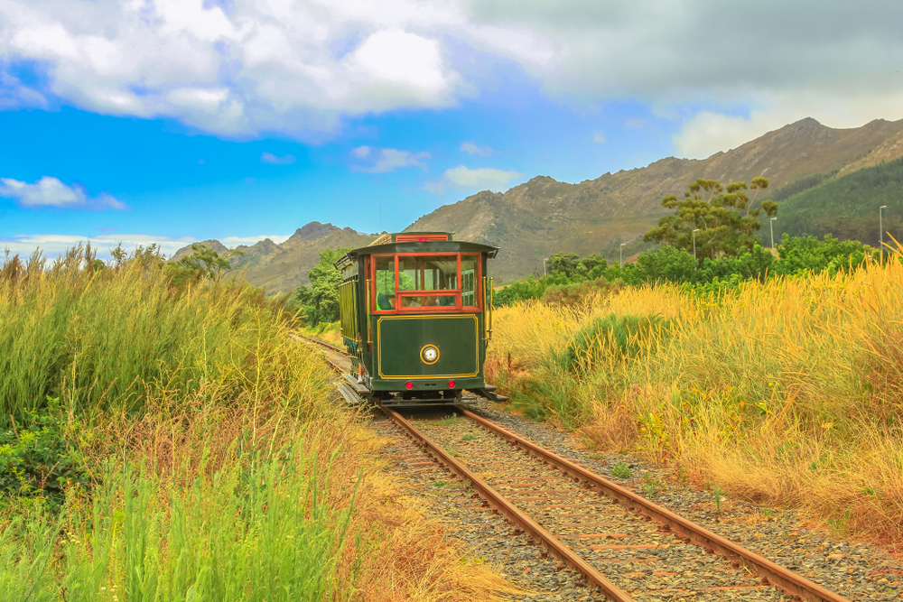 Franschhoek Wine Tram hop-on hop-off tour, one of the best ways to discover Franschhoek Valley in scenic landscape of Wine Region, near Cape Town, South Africa.