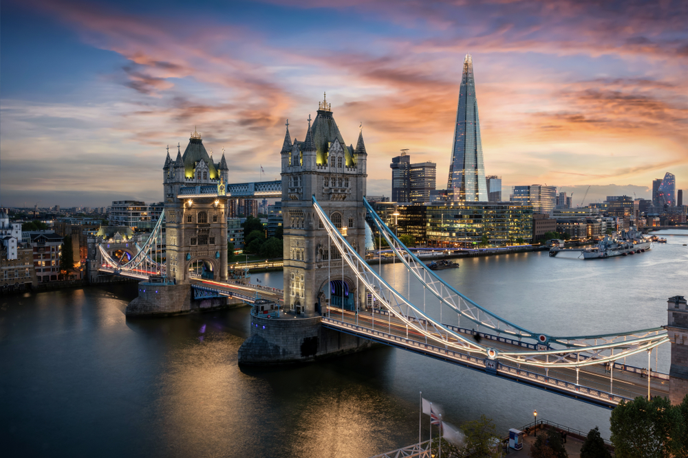 Aerial view to the illuminated Tower Bridge and skyline of London, UK, just after sunset