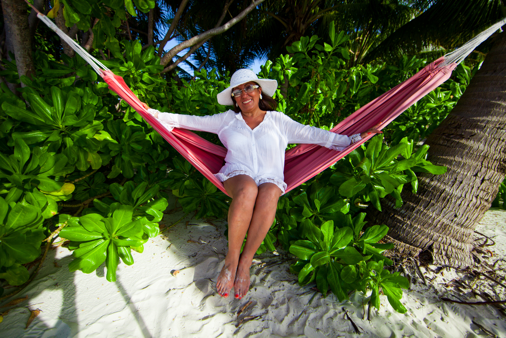 older woman relaxing on a hammock in a tropical destination