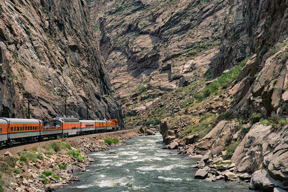 Train riding deep in the royal gorge beside the arkansas river in Colorado. Orange engine beside rushing blue water with rocky cliffs all around