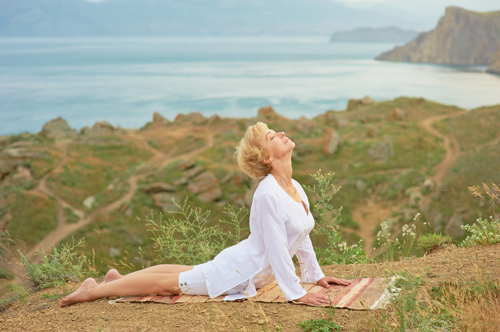 Senior woman doing yoga exercises with beautiful mountain view on the background