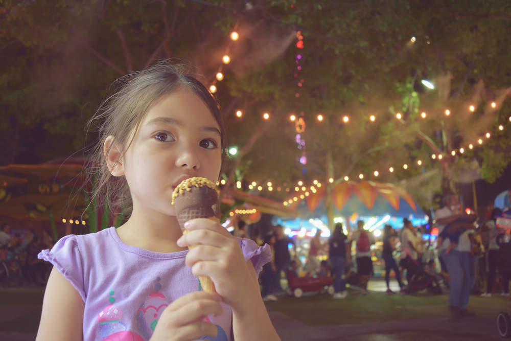 little girl enjoy eating ice cream at Texas state fair, filtered tones