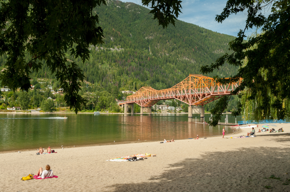 Nelson, British Columbia, Canada  one of TravelAwaits' best international small towns: The Rotary Lakeside Park public beach on a summer afternoon and the Highway 3A bridge crossing over West Arm of Kootenay Lake.